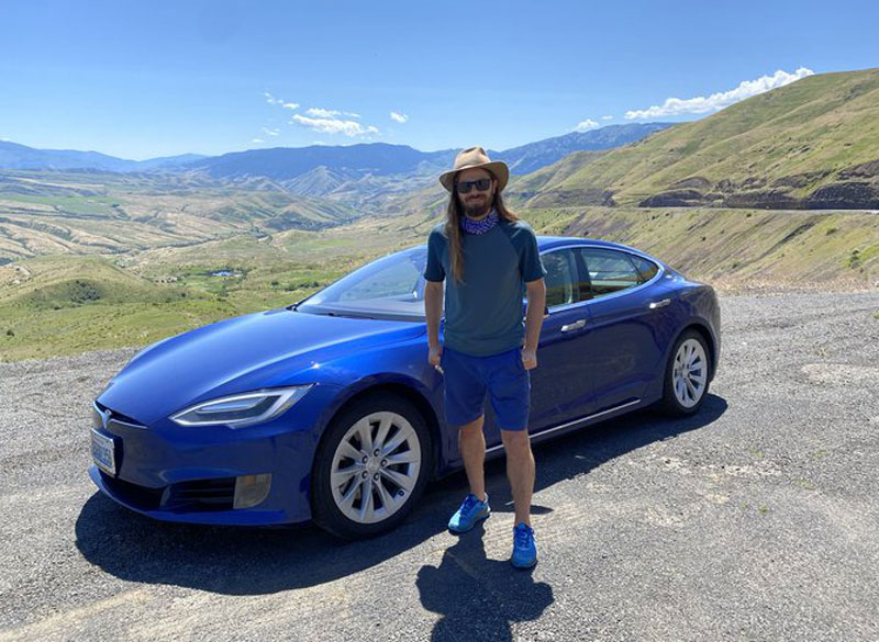 Фото: Ден Прайс на фоні Tesla – автівку йому подарували співробітники, як подяку за рішення не купувати собі авто заради підвищення зарплатні підлеглим/Dan Price/Ain.ua
